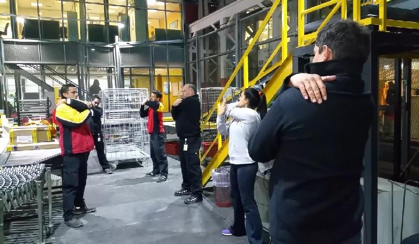 trabajadores de dhl haciendo pausa activa